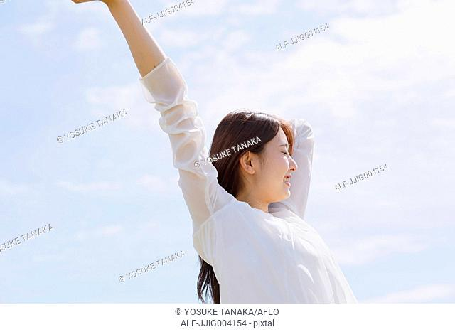 Young Japanese woman stretching arms