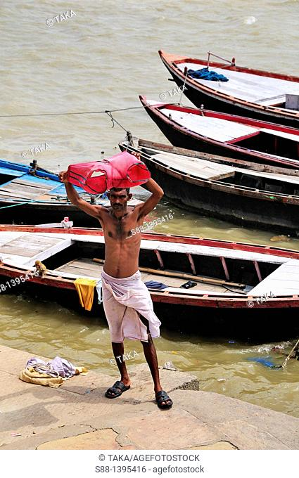 Man drying cloth after bathing at the ghat by the Ganges river