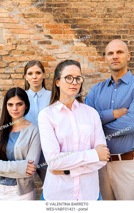 Portrait of confident business team at brick wall