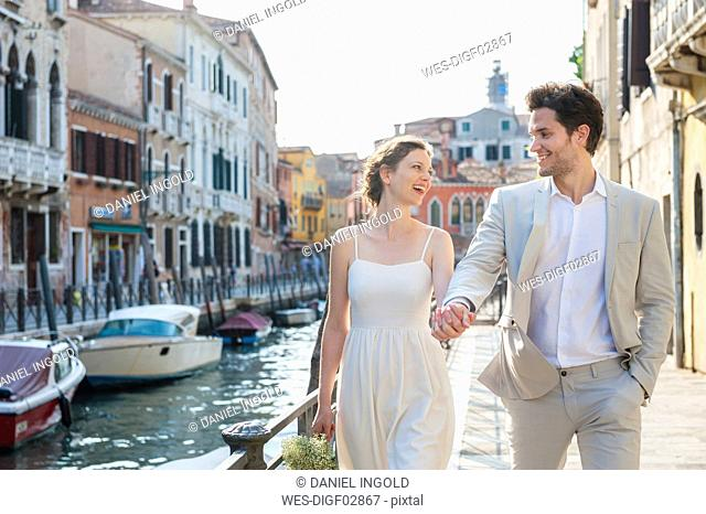Italy, Venice, happy bridal couple walking hand in hand at morning twilight