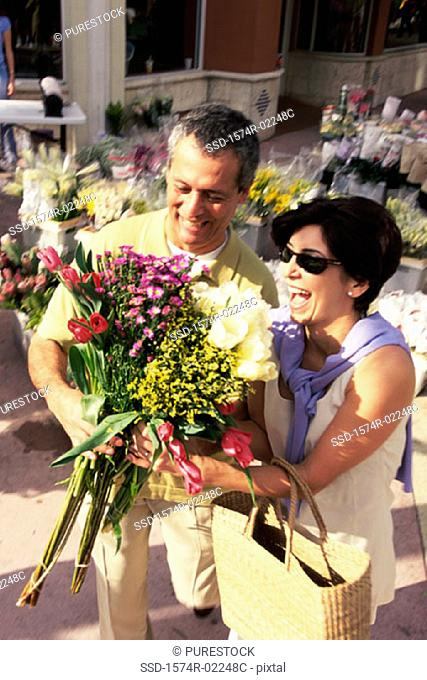High angle view of a mature couple holding a bouquet of flowers