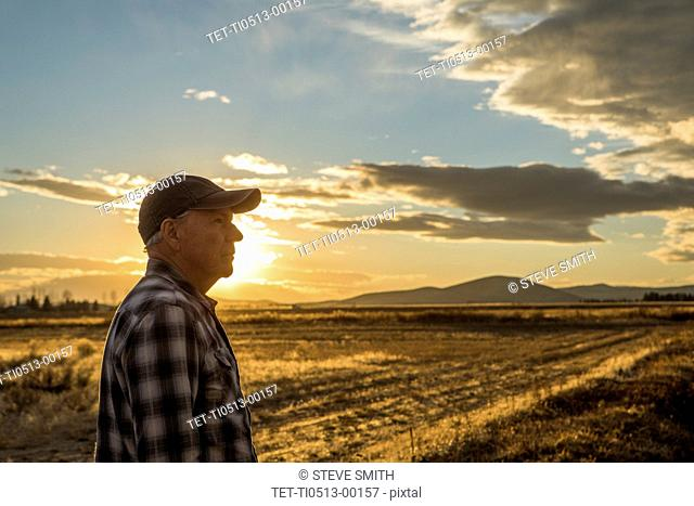 Senior man in baseball cap at sunset