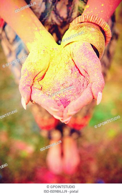 Waist down view of young boho woman with coloured chalk powder in cupped hands at festival