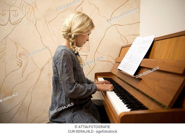Portrait of girl playing the piano in dining room