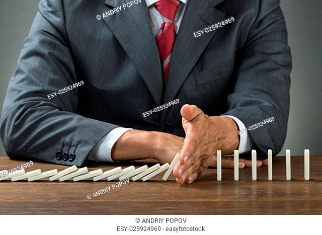 Midsection of businessman stopping dominoes falling on wooden desk