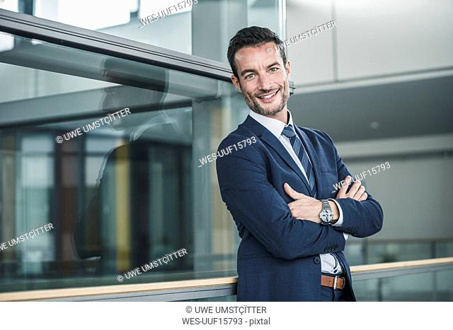 Portrait of a successful businessman, standing in office building, with arms crossed