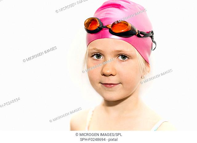 Portrait of a 6 year old girl with swimming goggles and cap