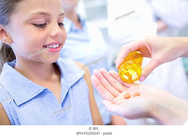 Doctor giving pills to girl