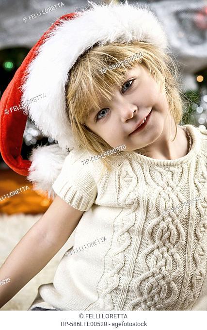 little girl wearing santa claus hat