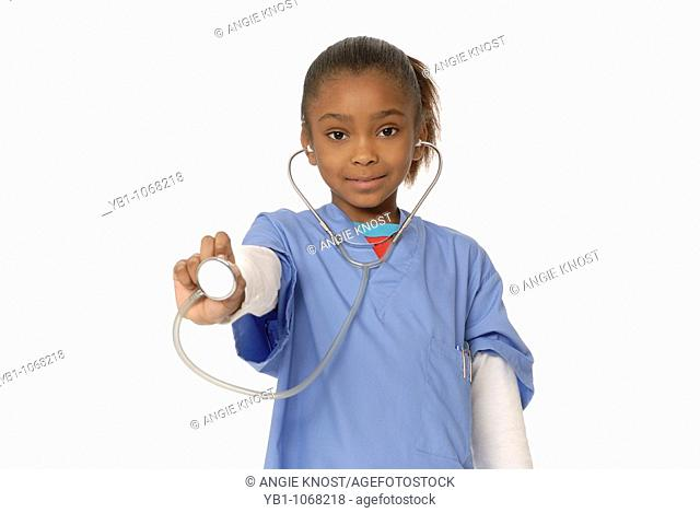 Six year old girl dressed as a doctor, using a stethoscope