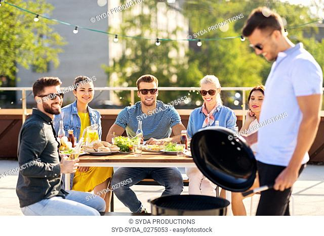 man grilling on bbq at rooftop party