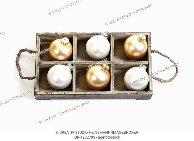 Gold and silver Christmas balls in a wooden box