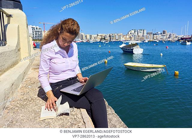 creative business woman enjoying her freedoom while working with notebook computer and book next to sea in holiday destination Malta