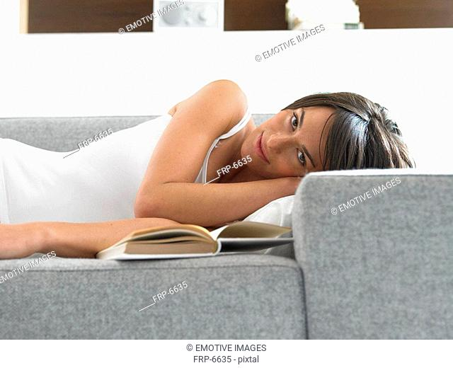 Woman lying on couch with book