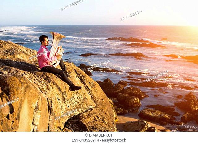 Musician playing the Tuba on the sea shore