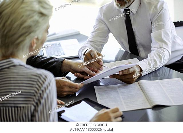 Businessman explaining document to colleagues