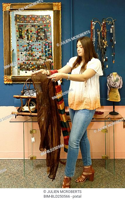 Caucasian woman examining scarf in store