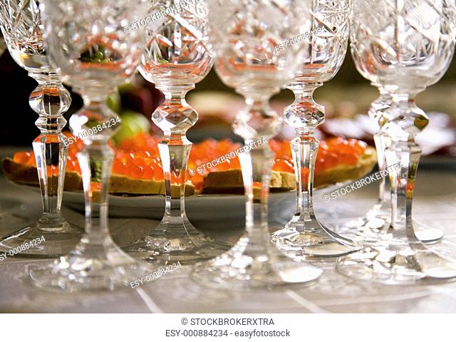 Close-up of crystal glasses necks on wedding table with tasty sandwiches at background