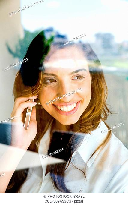 Young woman using smartphone, smiling, photographed through glass
