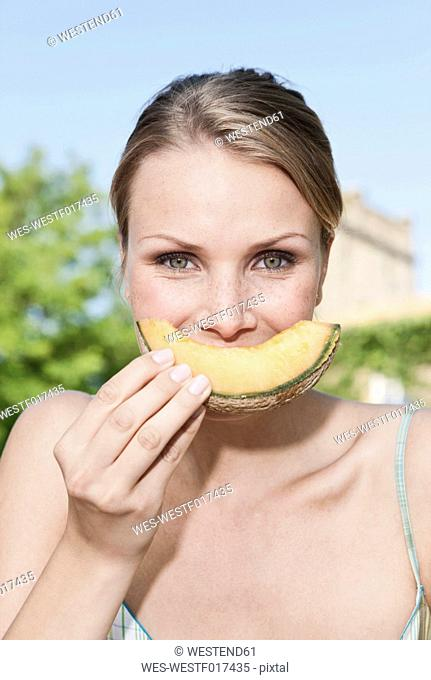 Italy, Tuscany, Magliano, Close up young woman eating honey melon, portrait