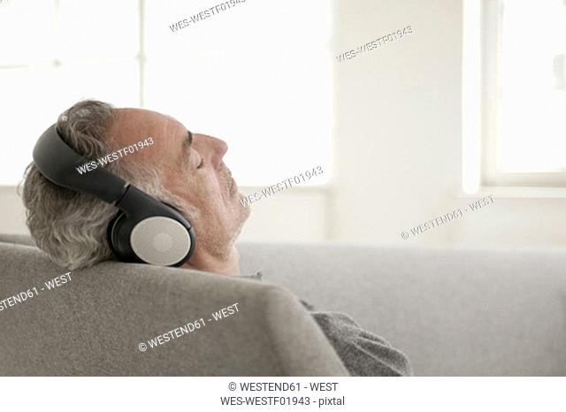 Mature man wearing headphones, eyes closed