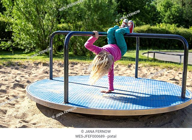 Blond little girl playing on playground