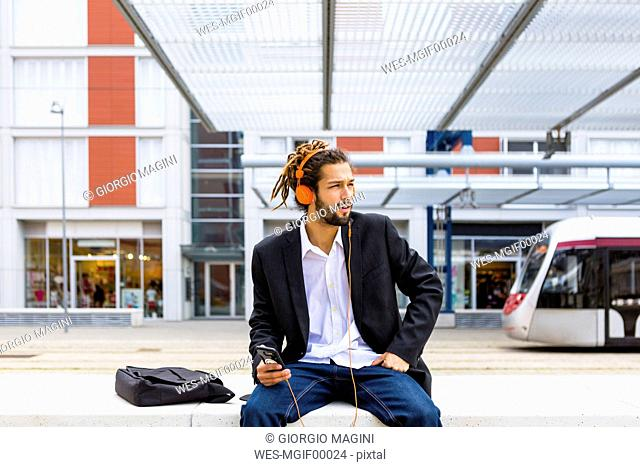 Young businessman with dreadlocks listening music with headphones and cell phone at station