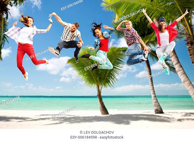 summer, sport, dancing, vacation and teenage lifestyle concept - group of teenagers jumping