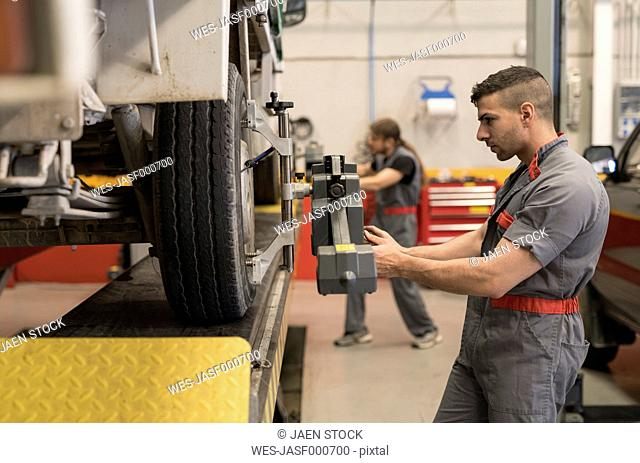 Mechanics calibrating wheels with computer and technology equipment