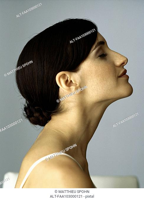 Woman with chignon, eyes closed, profile