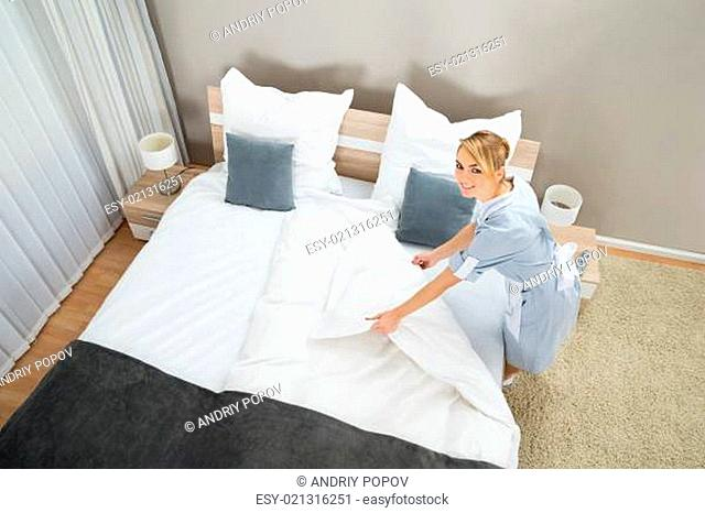 Female Housekeeper Making Bed With Bed Clothes In Hotel Room