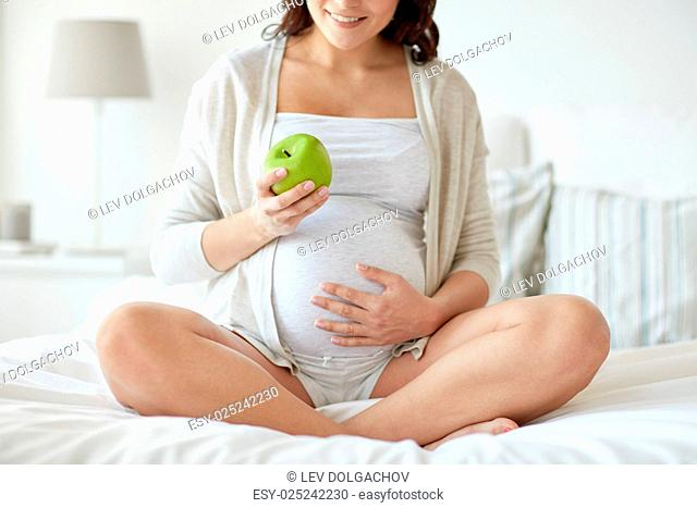 pregnancy, healthy food and people concept - close up of happy pregnant woman eating green apple at home