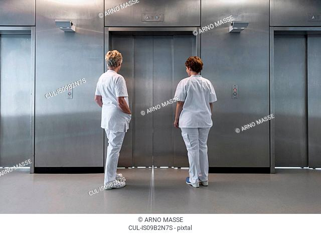 Rear view of nurses in hospital waiting for elevator