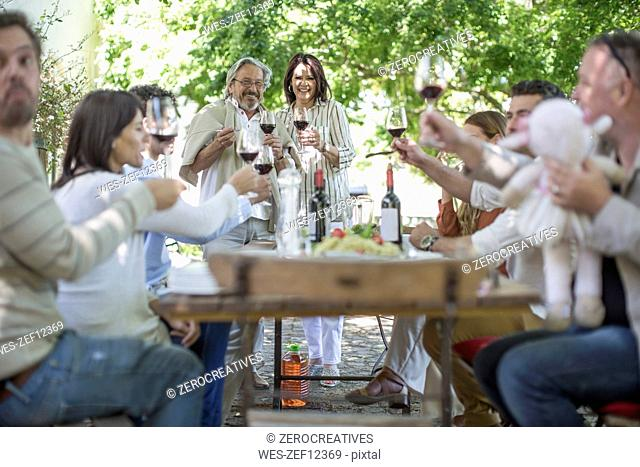 Happy friends and family having lunch in garden with red wine