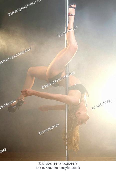 Portrait of a young elegant female pole dancer posing upside down
