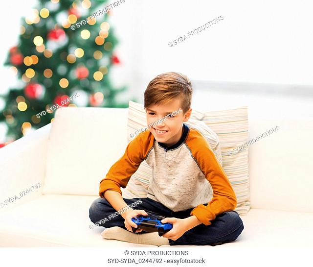 boy with gamepad playing video game at christmas