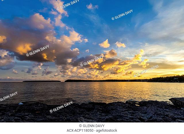 Clouds at sunrise with contrail above, overlooking Georgian Bay, Tobermory, ON, Canada