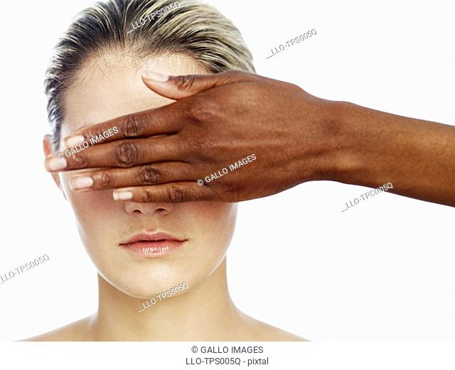 Woman With Another Woman's Hand Covering her Eyes  Studio Shot