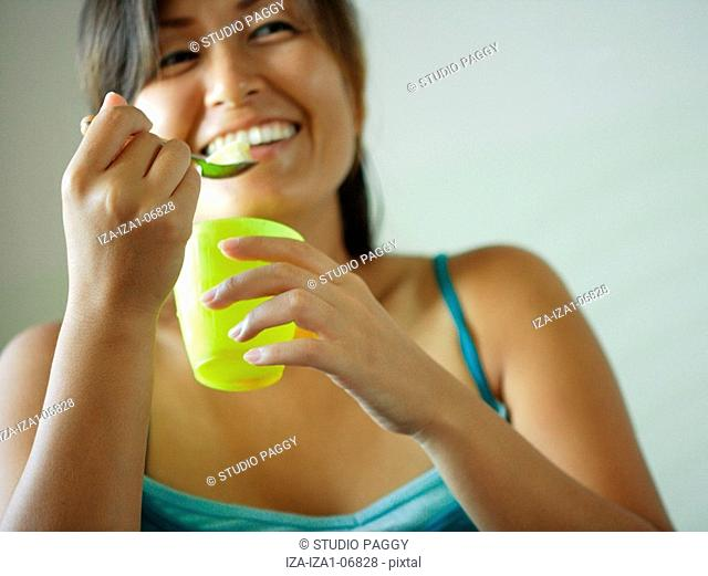 Mid adult woman eating egg pudding and smiling