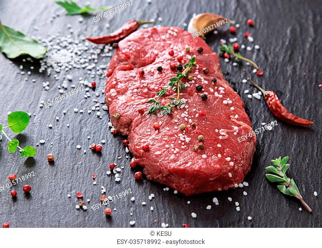 Delicious raw beef steak on black stone table, close-up