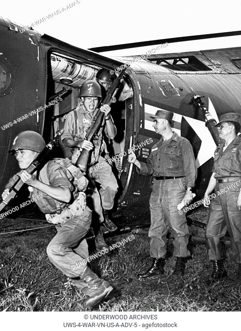 Vietnam: March, 1962 Vietnamese infantrymen pour out of a Piasecki H-21C Shawnee helicopter as their U.S. Army advisor instructor look on