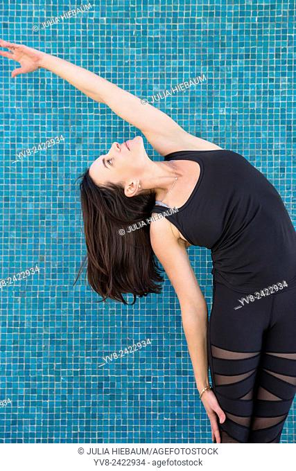 Standing side stretch Yoga pose with a turquoise background, San Diego, California