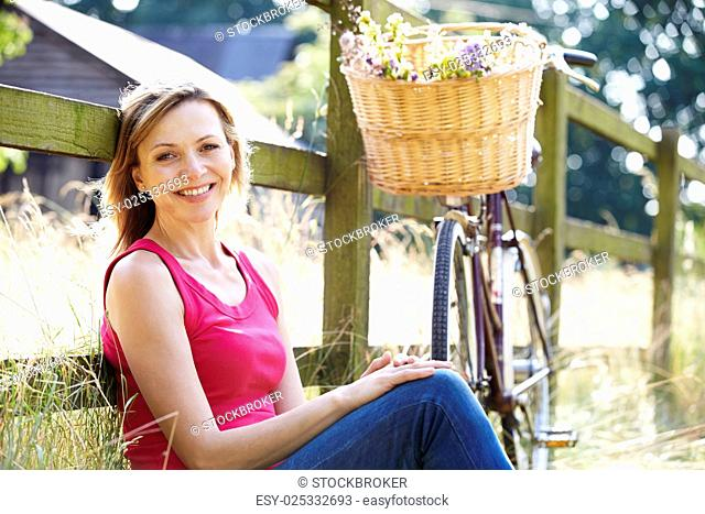 Attractive Woman Relaxing On Cycle Ride In Countryside