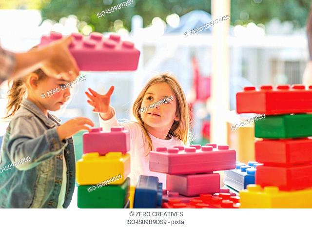 Two young children, outdoors, playing with foam building blocks