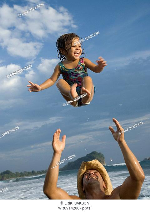Father playing with young daughter on beach