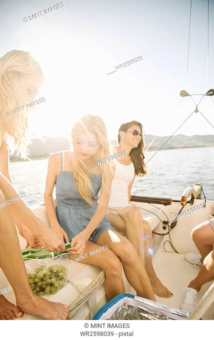 Mother and her two blond daughters sitting on a sail boat