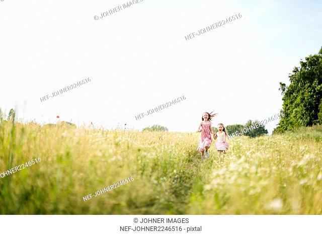 Girls running in meadow