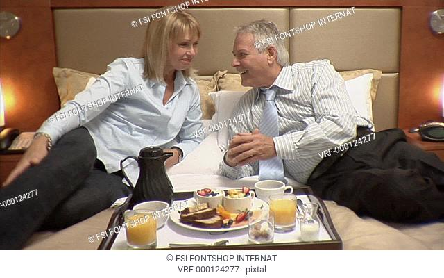 Medium lockdown shot high angle view of a well dressed couple reclining on a hotel bed while eating