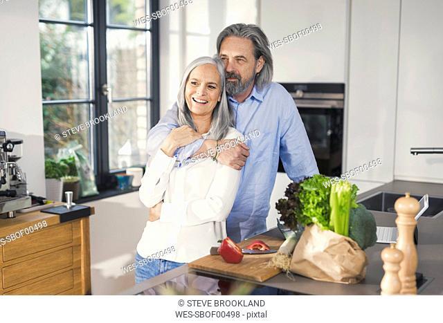 Happy senior couple preparing food in kitchen