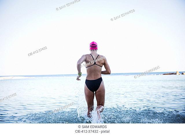 Female open water swimmer running into ocean surf